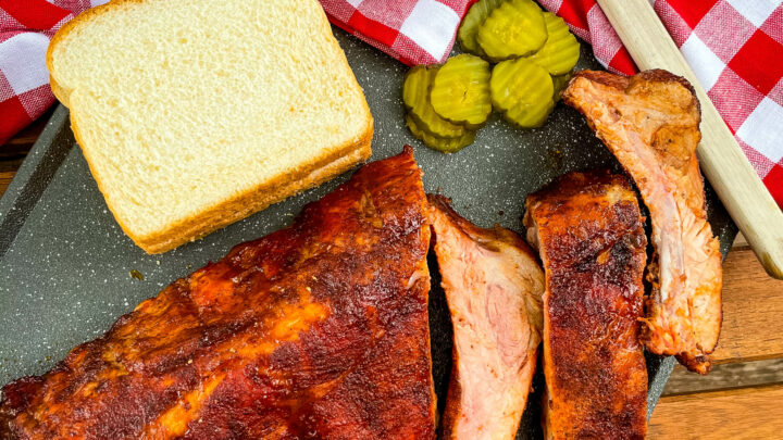 baby back ribs on a plate with bread, BBQ sauce, and pickles