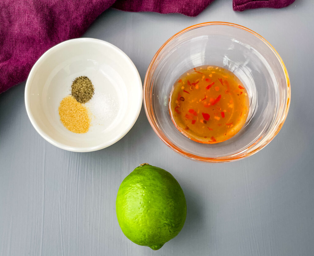 sweet chili sauce, a fresh lime, garlic powder and salt and pepper in bowls