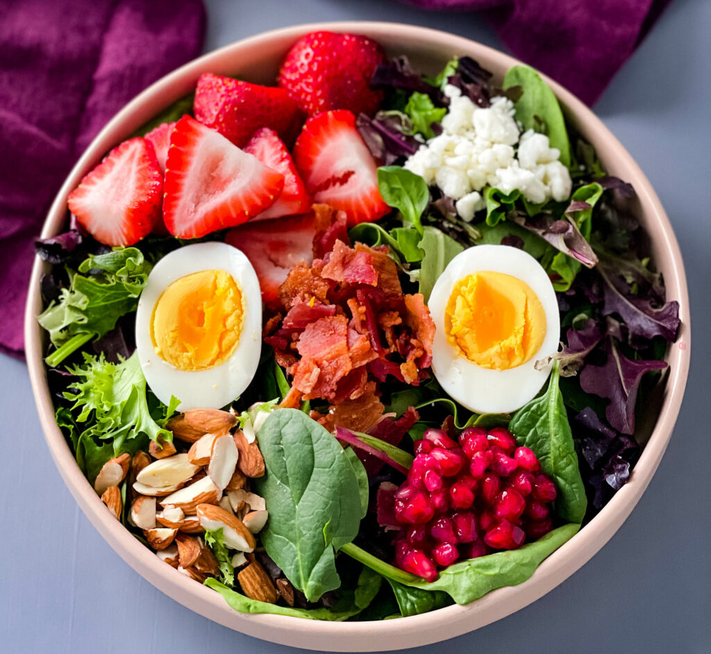 healthy breakfast salad in a bowl with bacon, eggs, and strawberries
