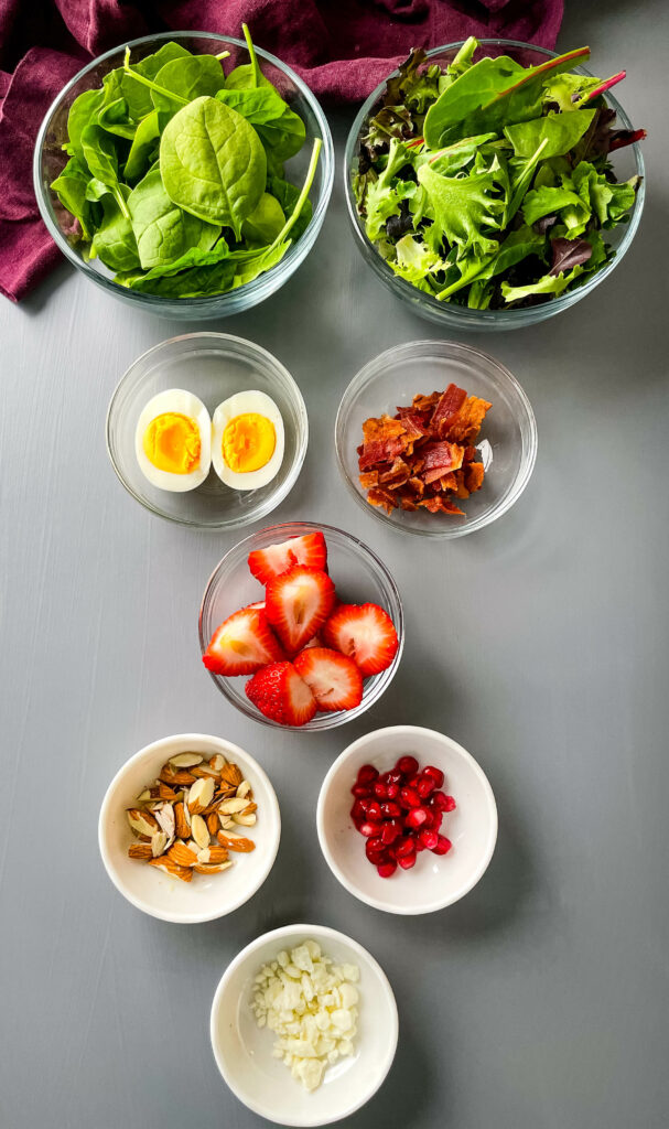fresh spinach, fresh mixed greens, boiled eggs, pomegrante seeds, feta cheese, strawberries, and almonds in separate bowls