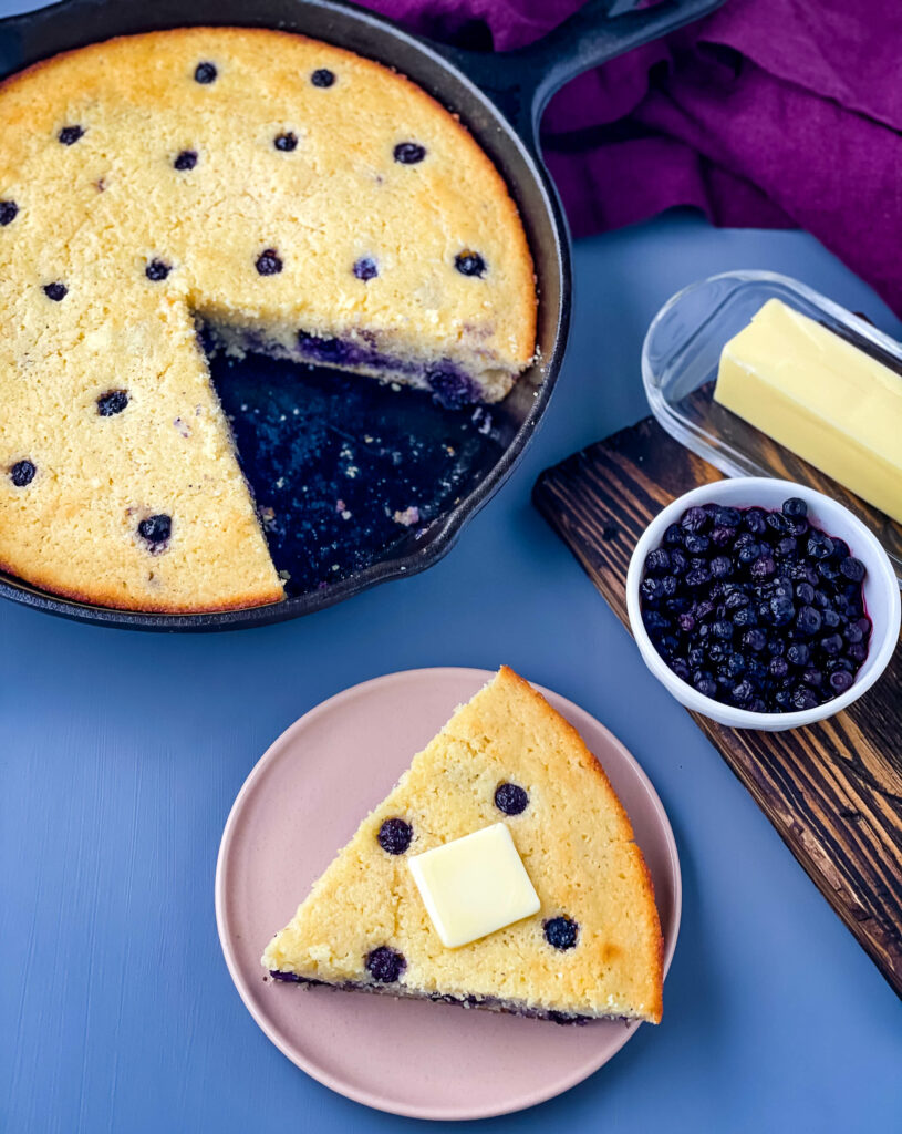 a slice of homemade blueberry cornbread on a plate with a pan of cornbread