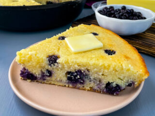 a slice of homemade blueberry cornbread on a plate