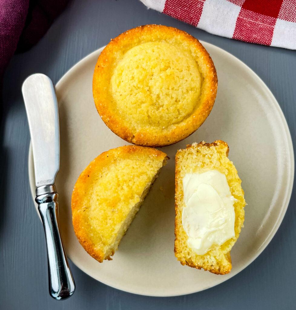 cornbread muffin sliced in half drizzled in butter