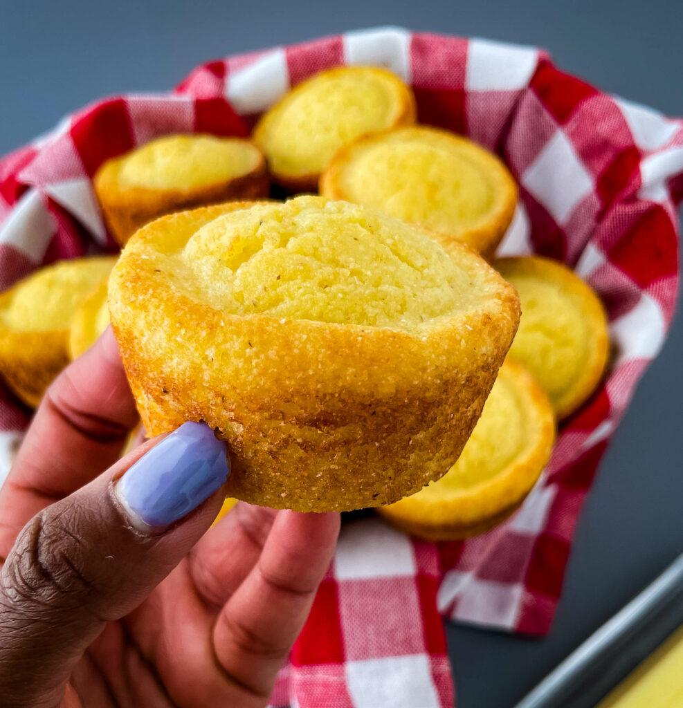 person holding cornbread muffin