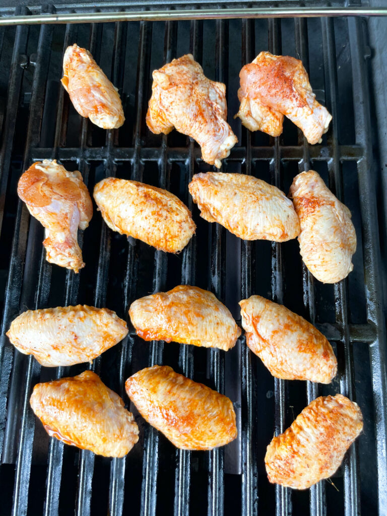 raw chicken wings on a grill