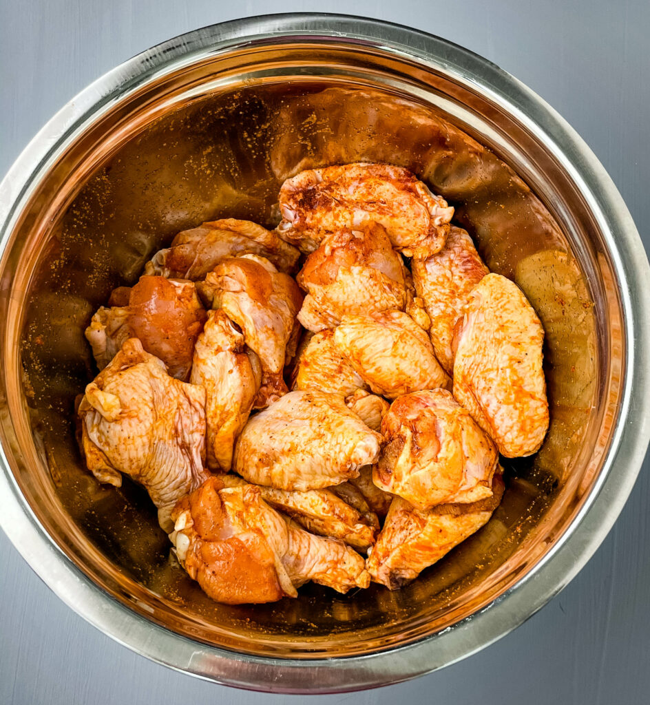 raw chicken wings in a large bowl with seasoning