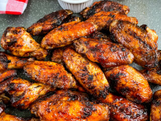 grilled chicken wings on a plate with BBQ sauce