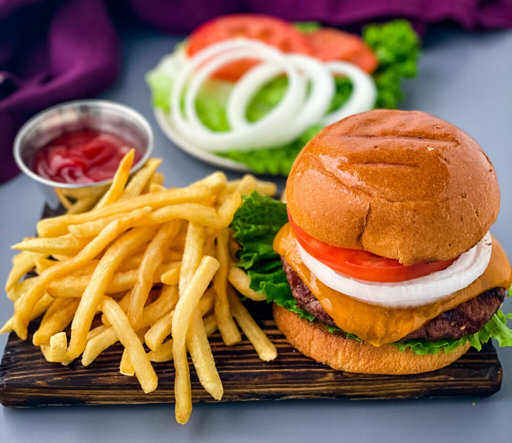 grilled cheeseburgers on a bun with a plate of fries