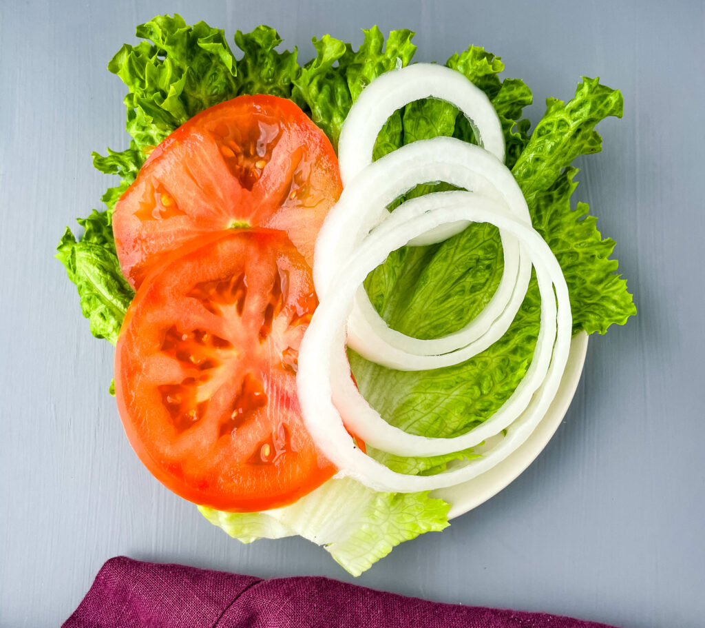 lettuce, sliced tomatoes, and sliced onions on a plate