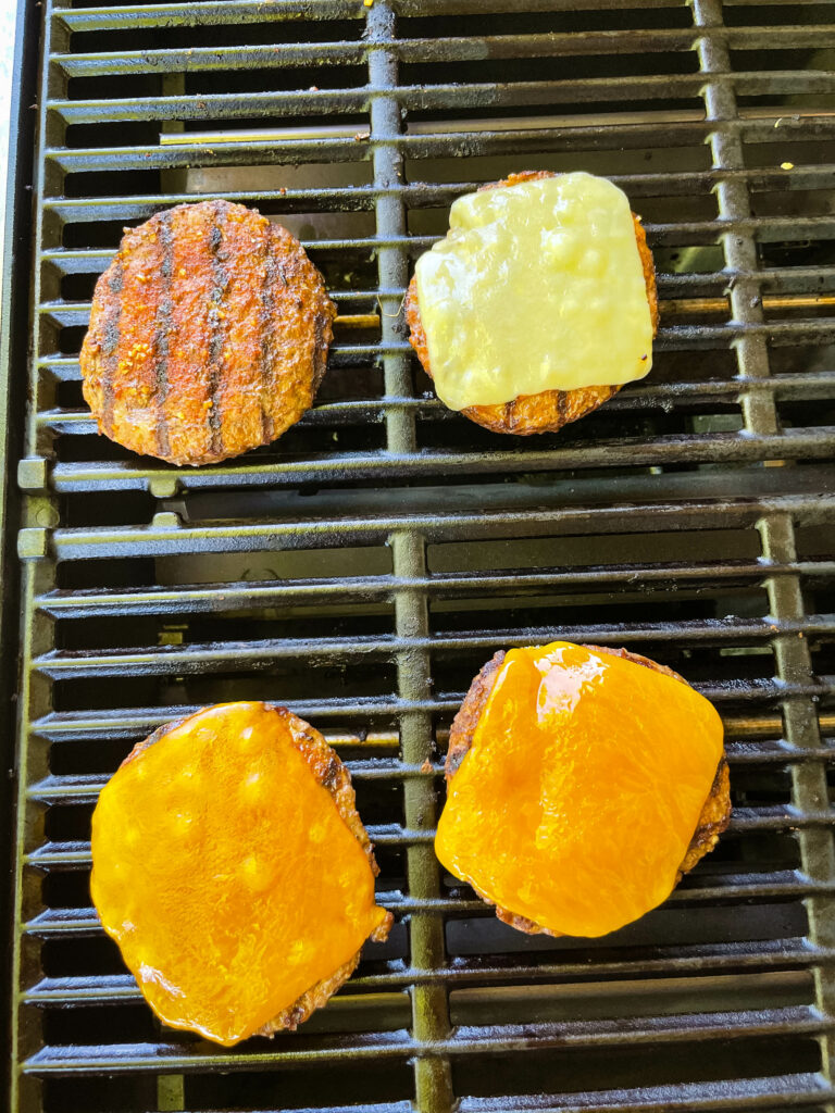 cooked hamburgers on a grill with cheese