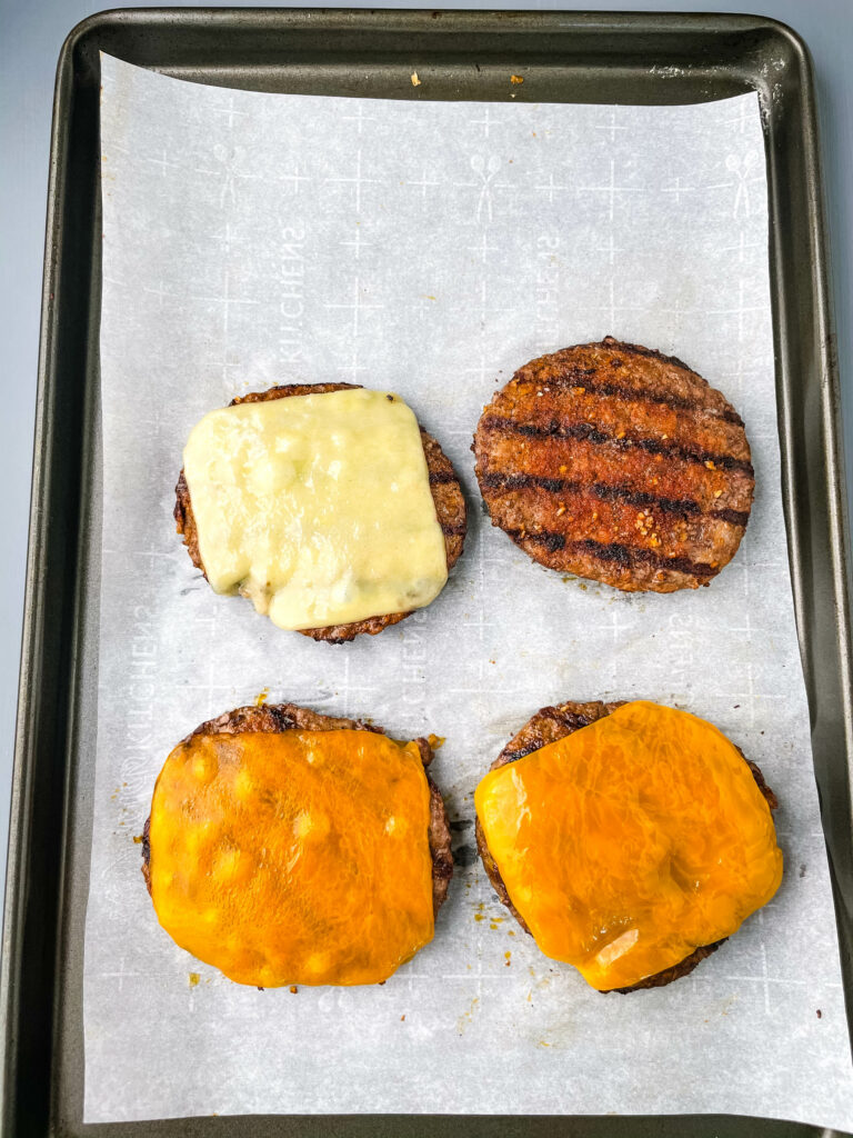 cooked cheeseburgers on a sheet pan