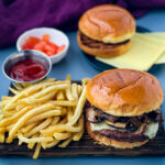 mushroom swiss burger on a plate with French fries