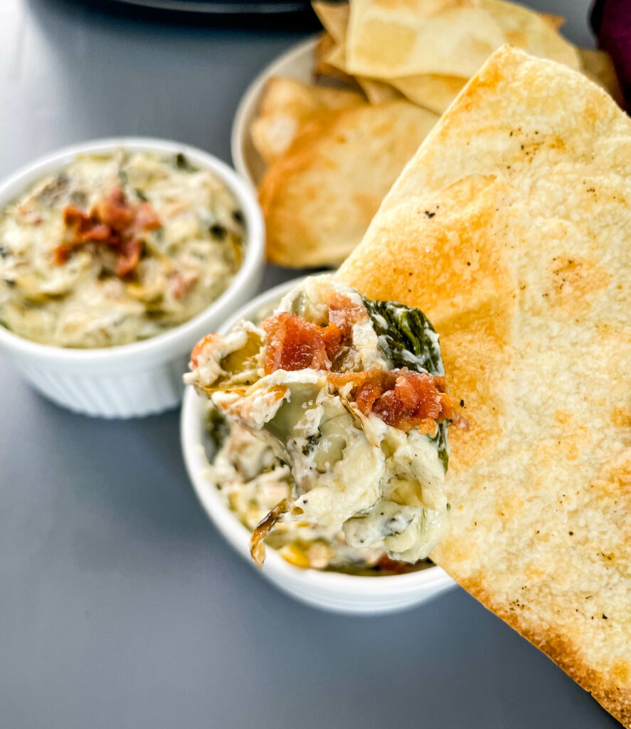 person holding bacon spinach artichoke dip on a chip