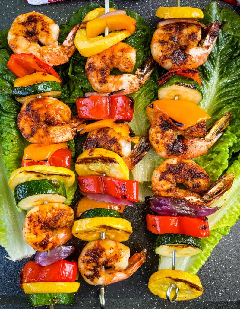 BBQ grilled shrimp skewers on a bed of lettuce