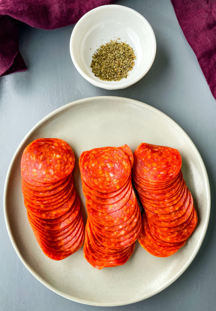 pepperoni on a plate with Italian Seasoning