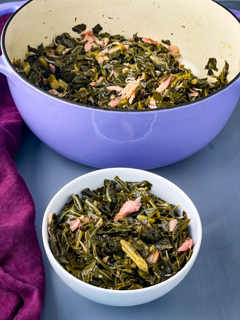 southern collard greens in a white bowl and a purple pot