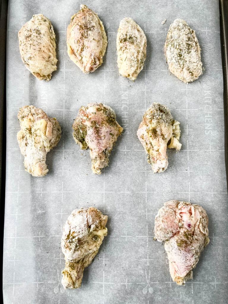 raw ranch chicken wings on a sheet pan with parchment paper