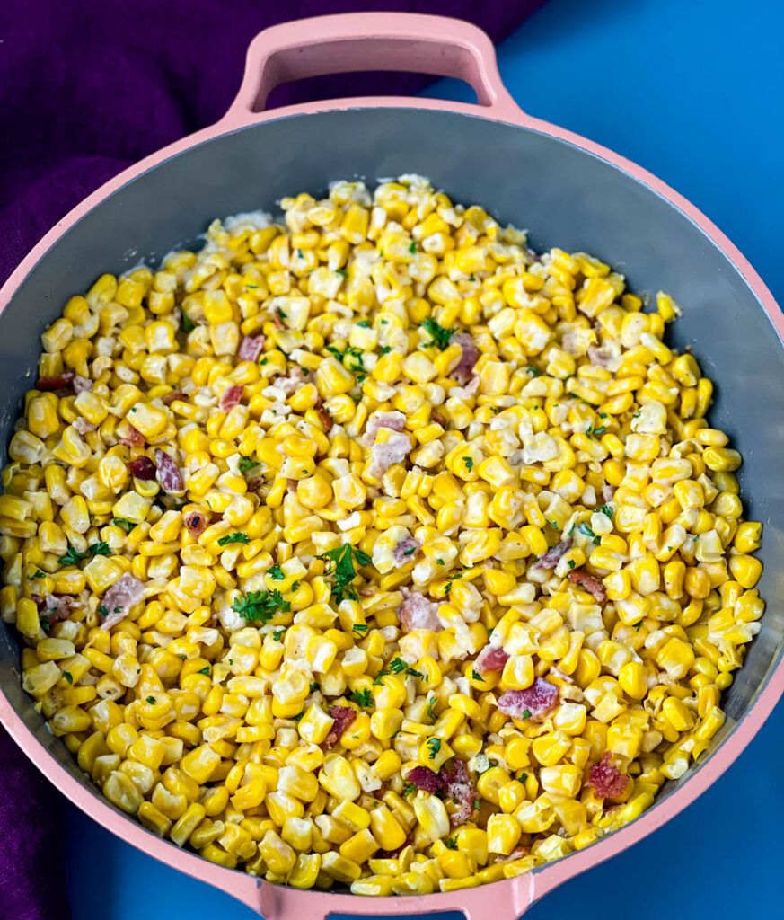 homemade creamed corn in a pink skillet