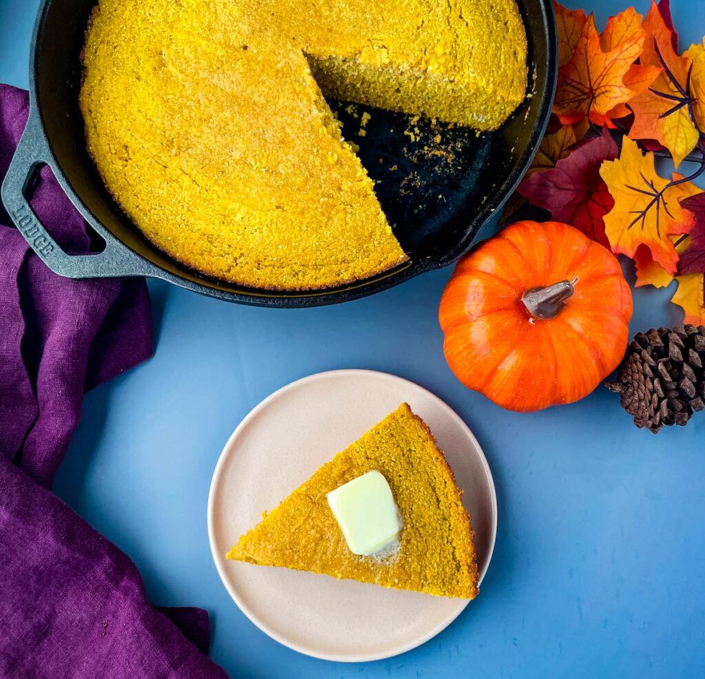 pumpkin cornbread on a plate with pumpkin cornbread in a cast iron skillet