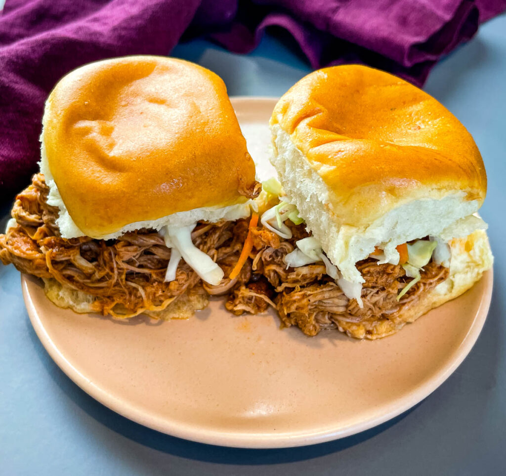 pulled pork sliders with coleslaw on a pink plate