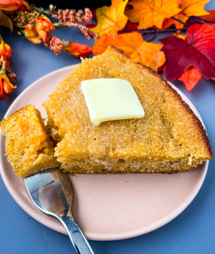 sweet potato cornbread with butter on a plate with a fork and small piece of cornbread