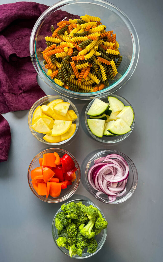 dry rotini pasta, broccoli, red peppers, yellow peppers, green peppers, and red onions in glass bowls