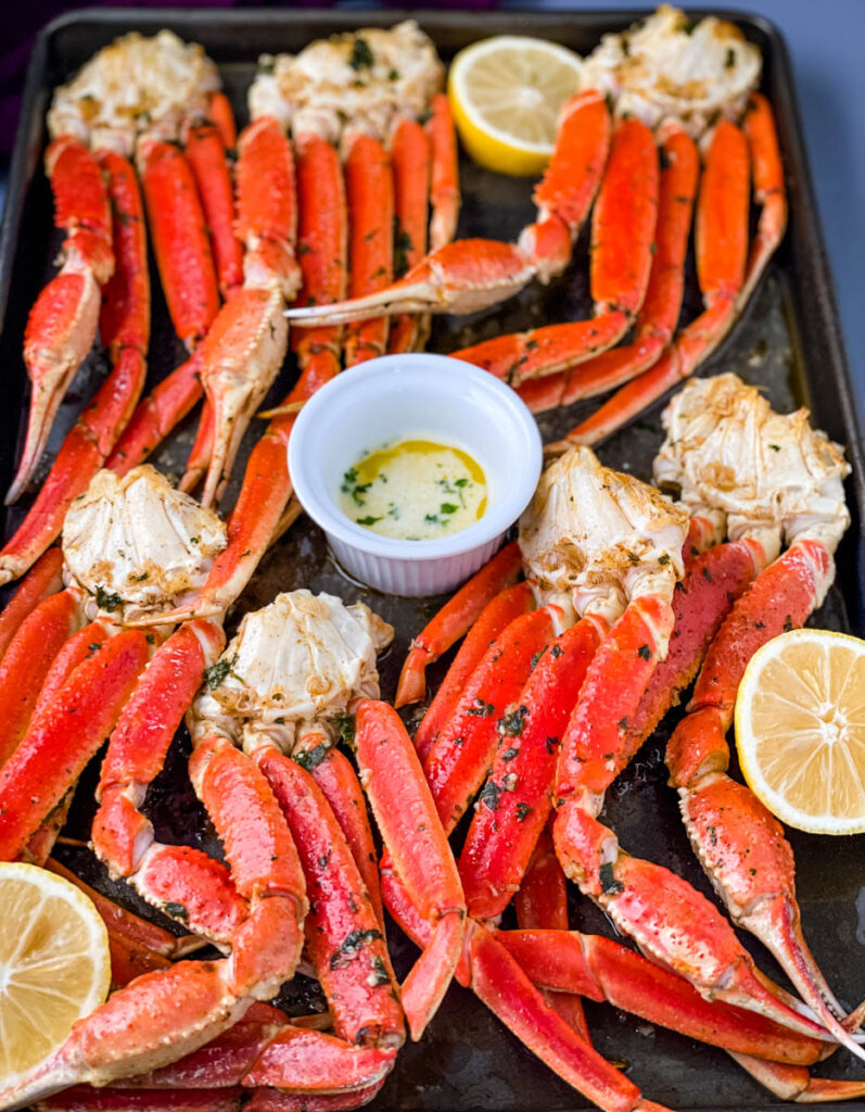 baked crab legs on a pan with lemon garlic butter