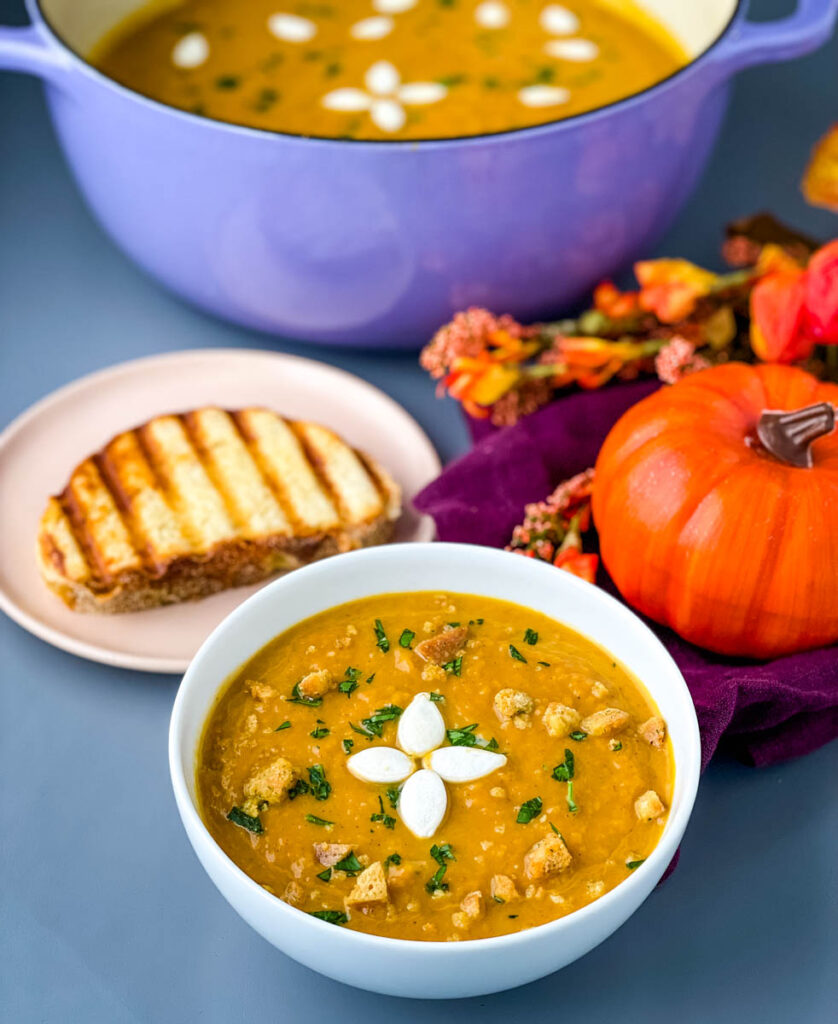 creamy canned pumpkin soup in a white bowl with a slice of bread