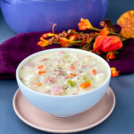 creamy ham, potato, and vegetable soup in a white bowl