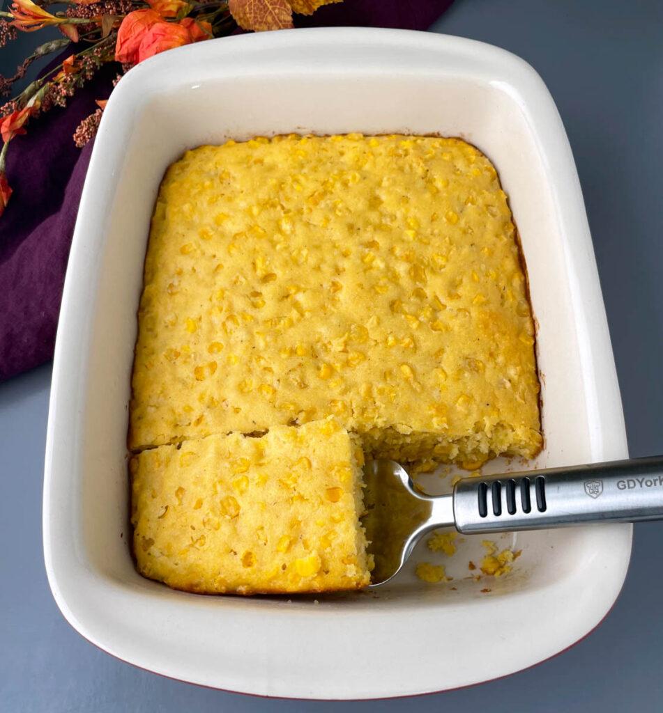 a slice of corn casserole in a baking dish
