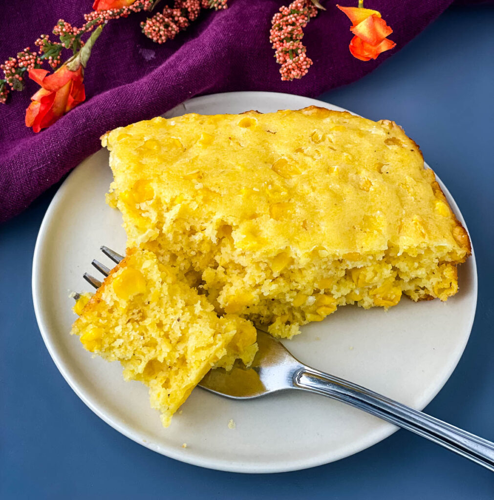 a forkful and slice of homemade cornbread casserole on a white plate