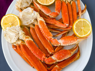 Instant Pot crab legs on a white plate with lemon