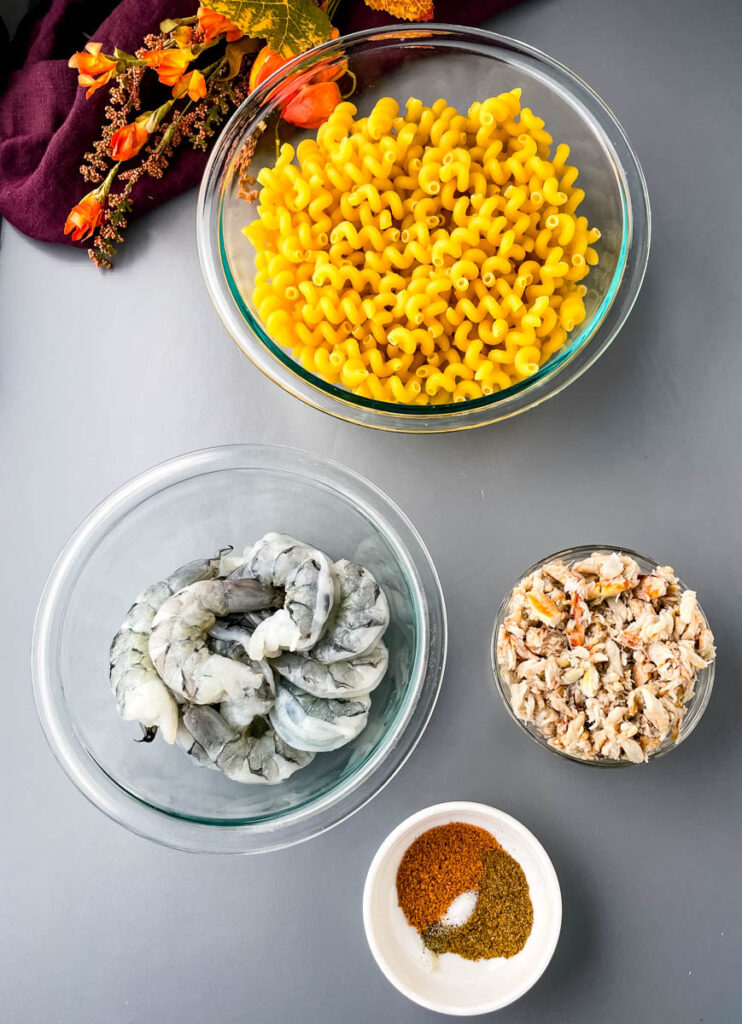 dry pasta, raw shrimp, crab, and spices in separate bowls