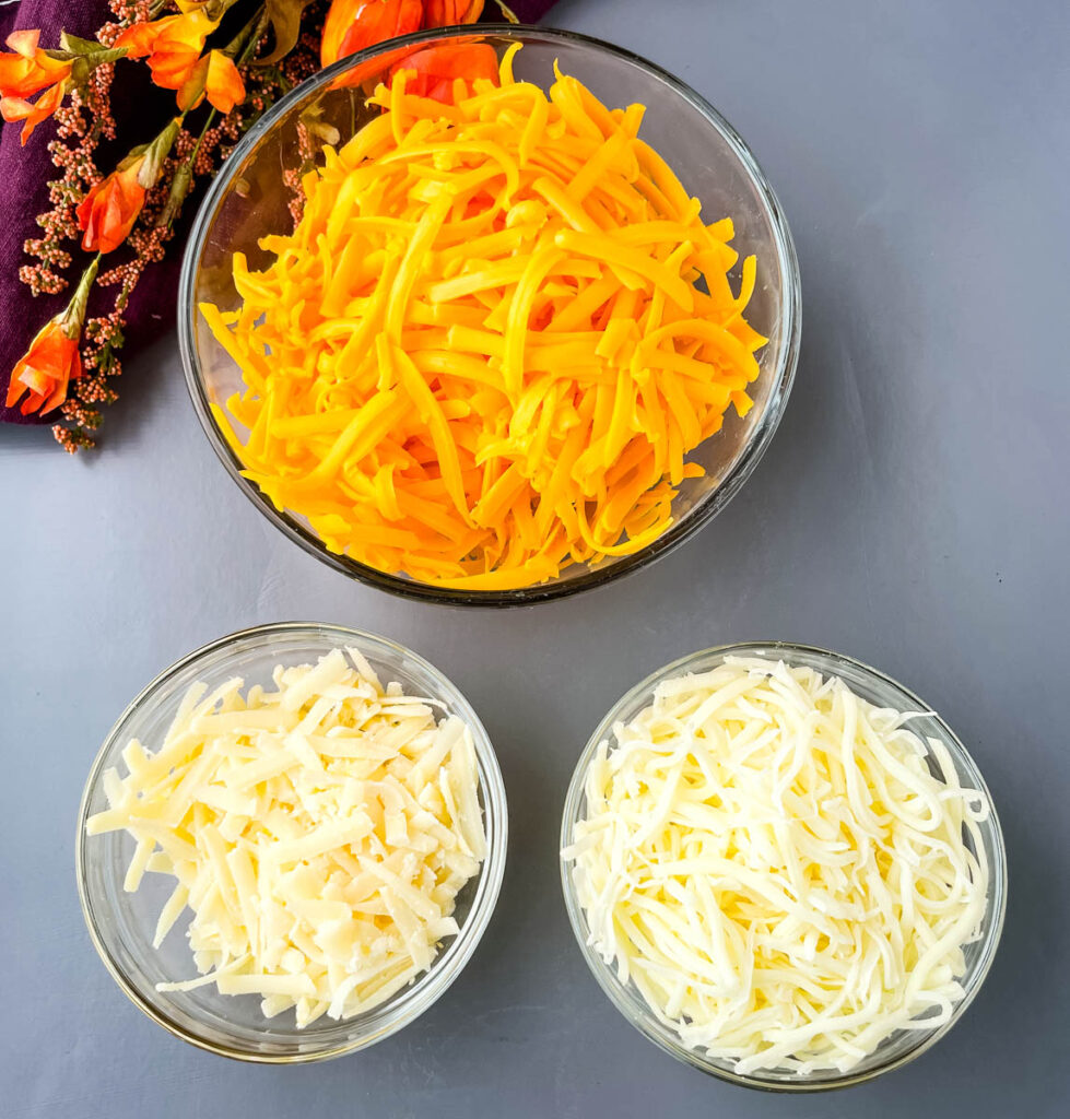 shredded cheddar cheese, mozzarella, and Parmesan cheese in glass bowls