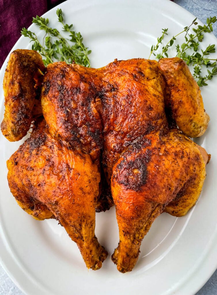 seasoned spatchcock chicken on a white plate