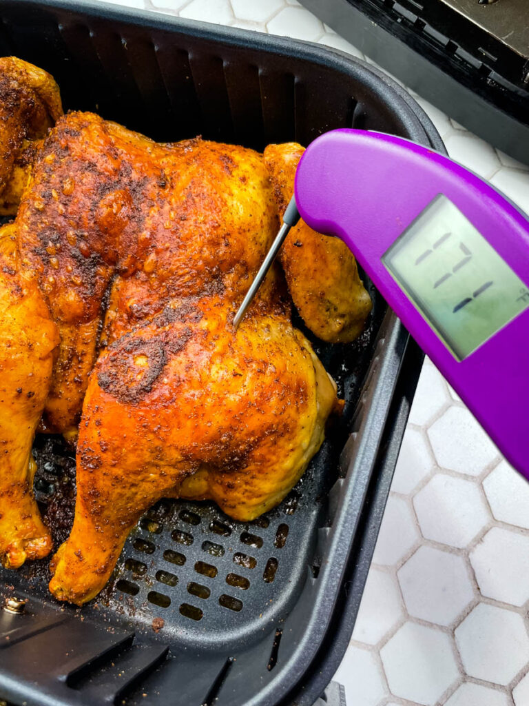 spatchcock chicken in air fryer with a meat thermometer showing 171 degrees