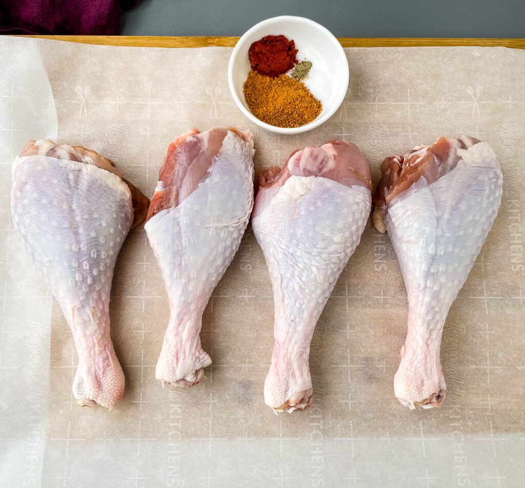 raw turkey legs on parchment paper with a bowl of seasonings