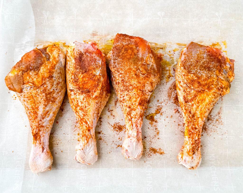 raw seasoned turkey legs on parchment paper