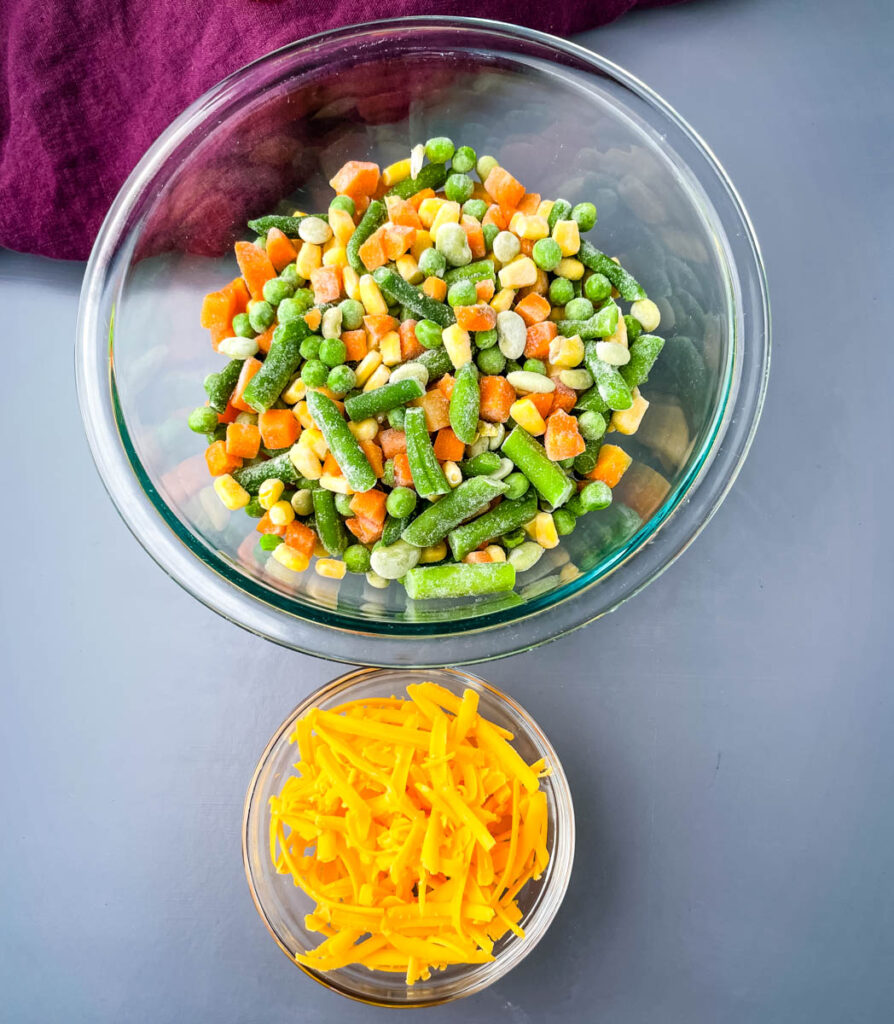 frozen mixed vegetables and shredded cheddar cheese in separate bowls