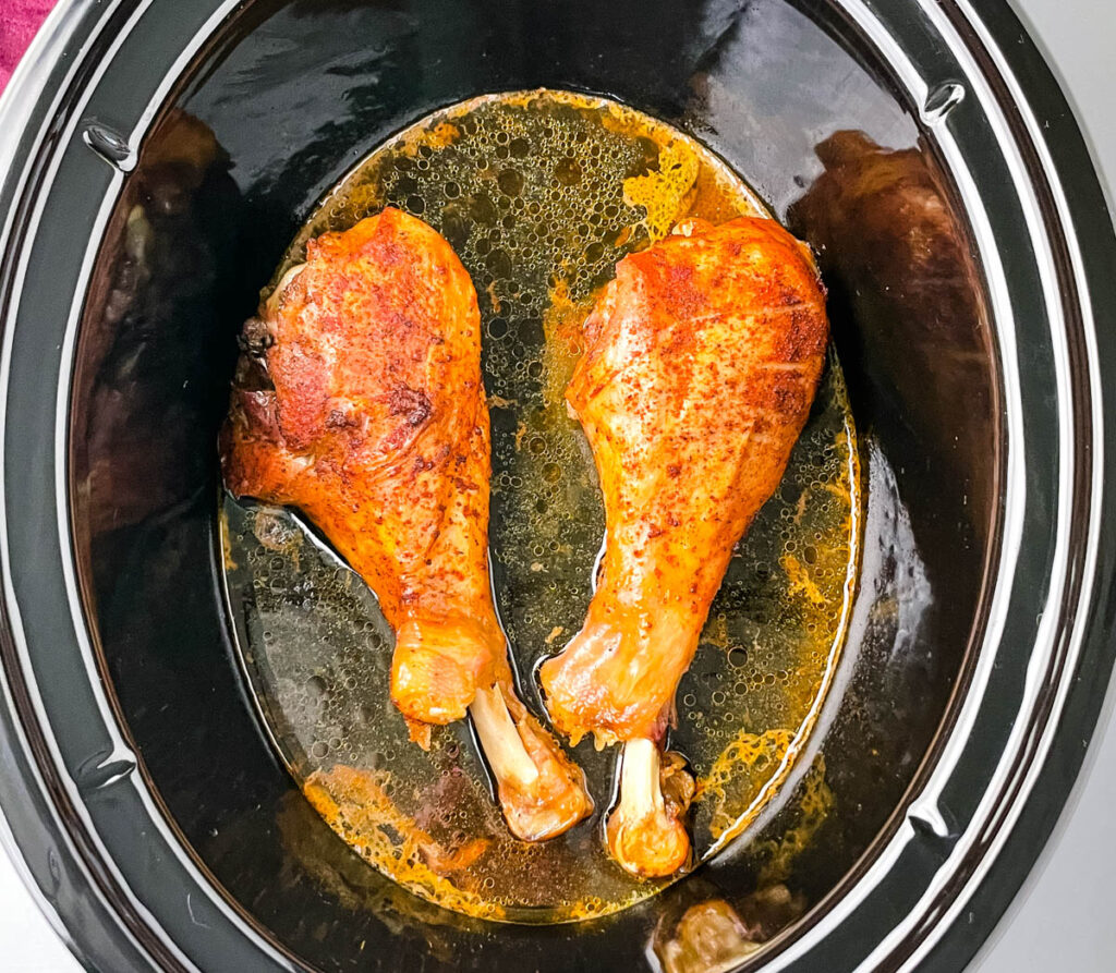2 cooked turkey legs in a Crockpot slow cooker