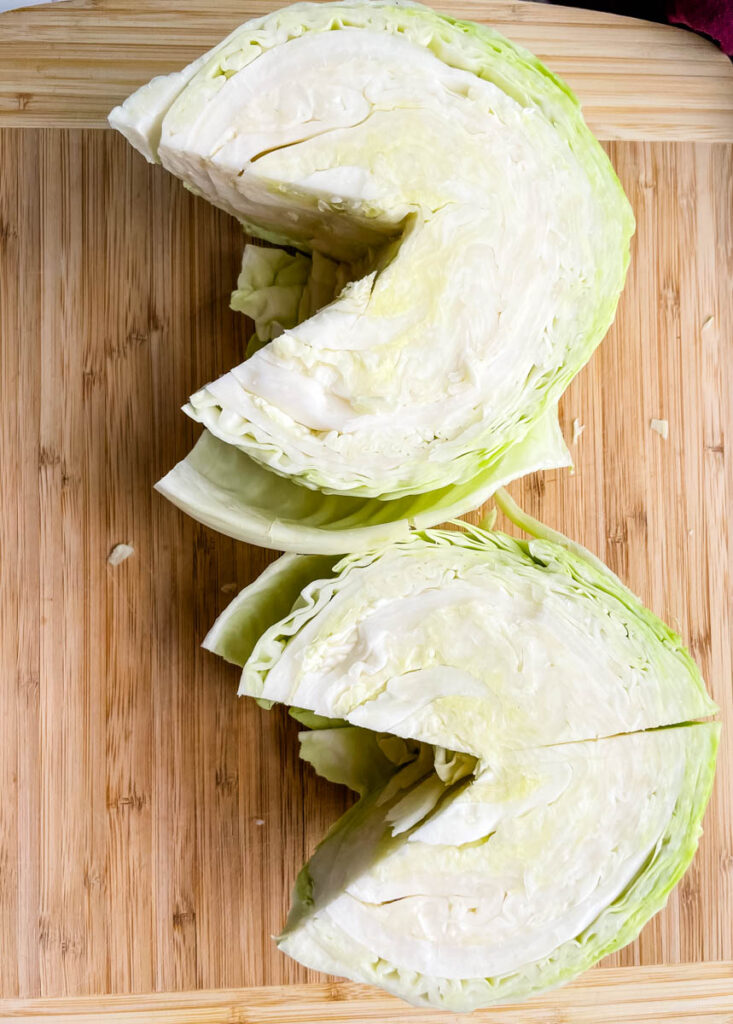fresh cabbage sliced into wedges on a cutting board