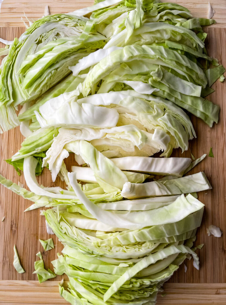 fresh cabbage sliced into strips on a cutting board