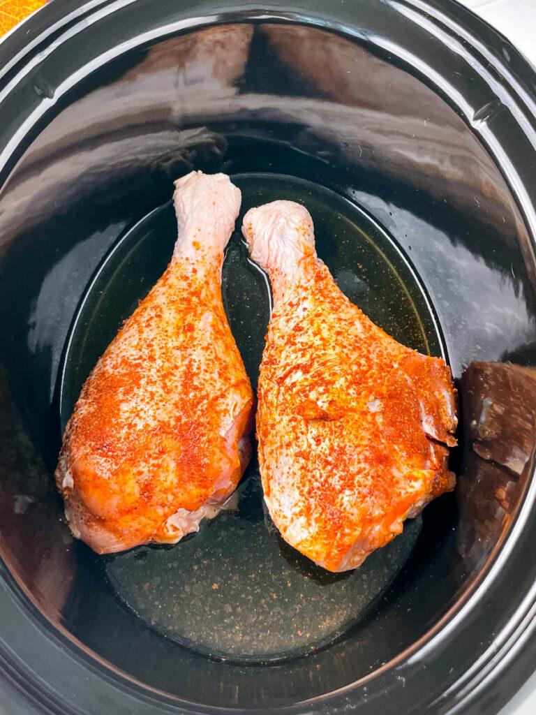 raw, seasoned turkey legs in a slow cooker