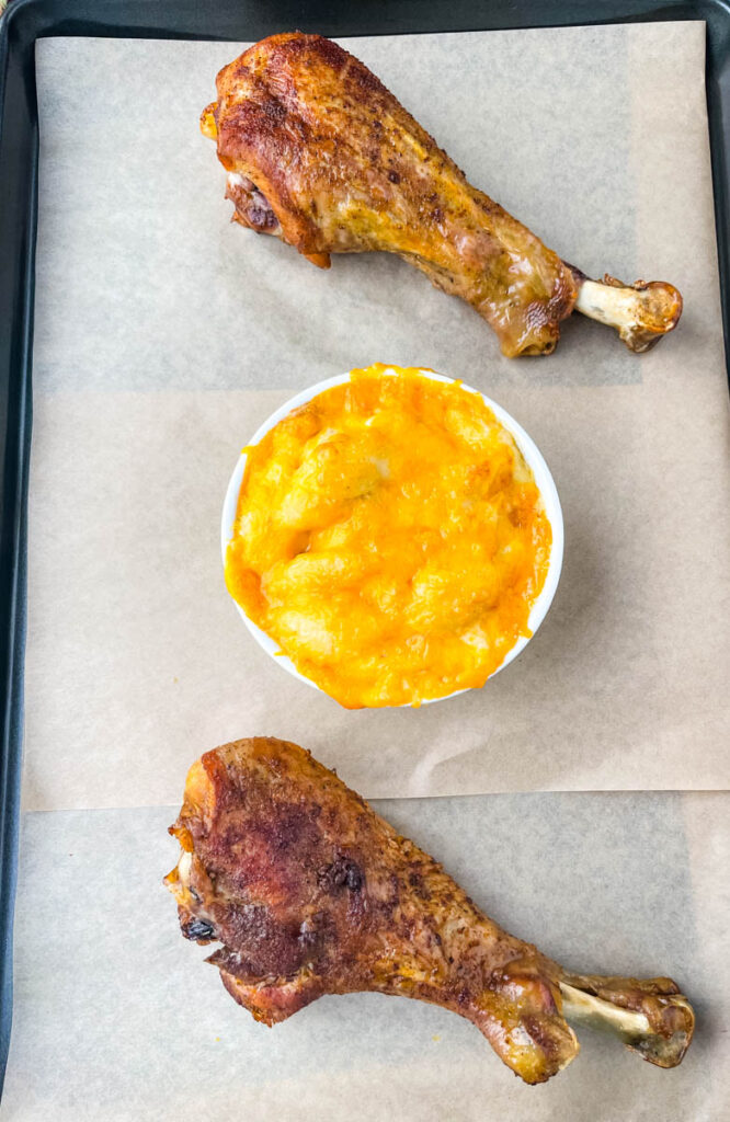 cooked turkey legs and mac and cheese on a flat surface