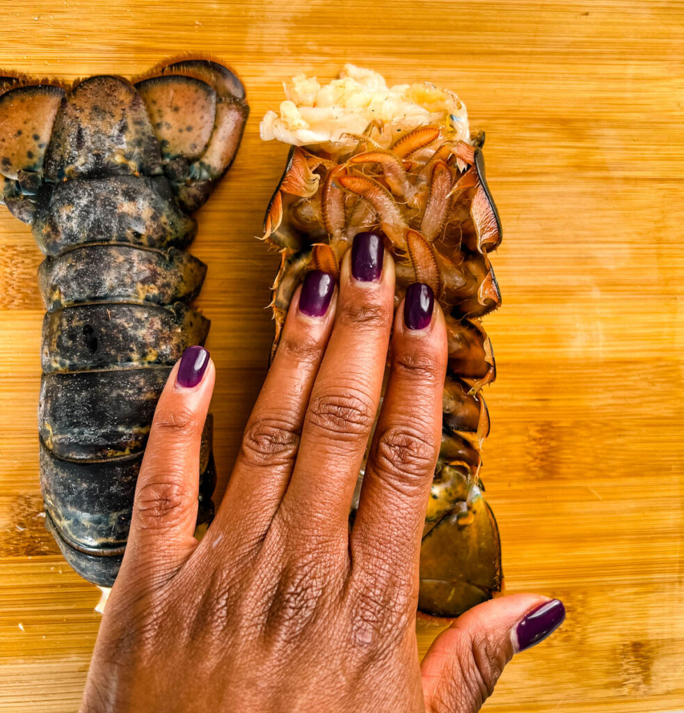 person pressing down on lobster tail