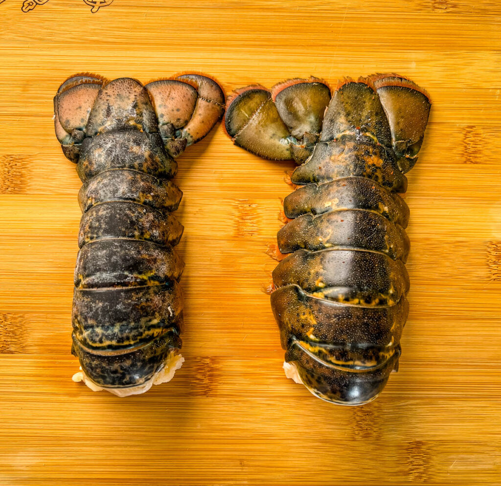 raw lobster tails on a cutting board