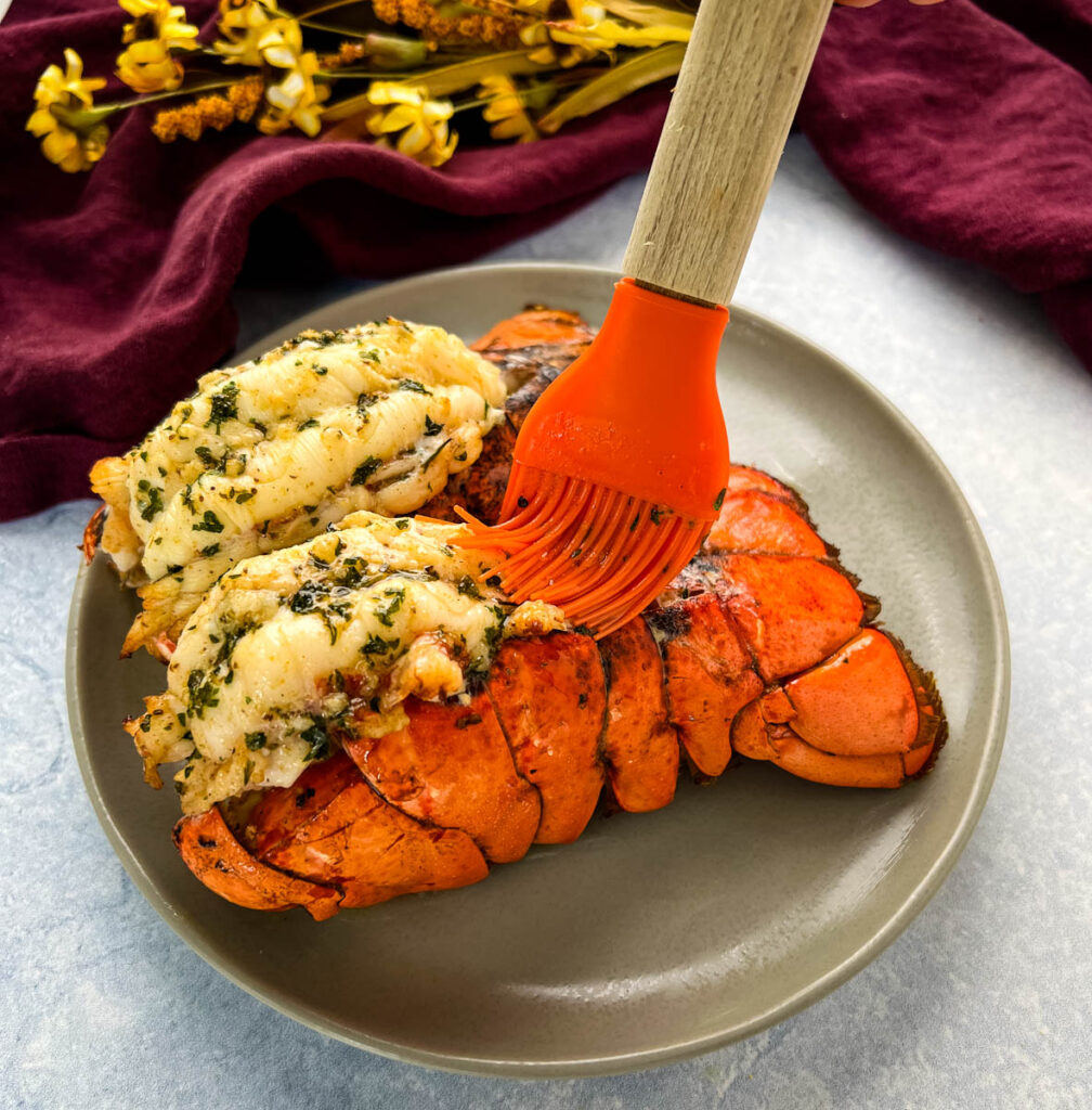 air fryer lobster tails on a white plate being drizzled with butter