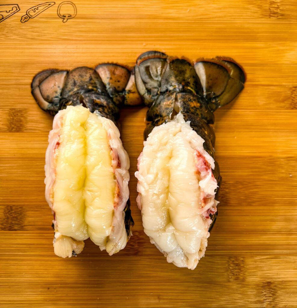 butterflied lobster tails on a wooden cutting board