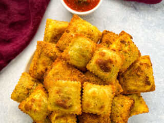 air fryer toasted fried ravioli on a plate with marinara sauce