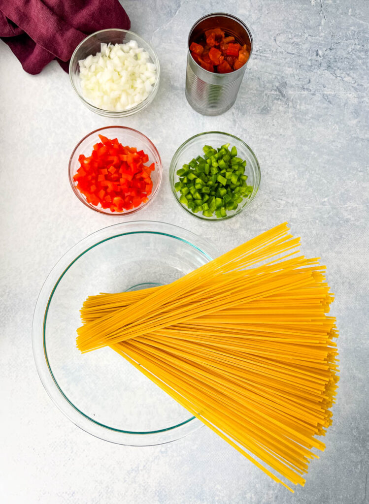dry spaghetti pasta, raw red peppers, green peppers, onions, fire roasted tomatoes on a flat surface
